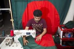 En ung skräddare Md Rashed Alam åldras 28 bangladeshiska nationsflaggor för danande på Dhaka, Bangladesh Arkivfoton