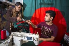 En ung skräddare Md Rashed Alam åldras 28 bangladeshiska nationsflaggor för danande på Dhaka, Bangladesh Royaltyfri Bild