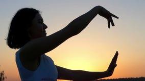 En ung slank kvinna gör vinkande förehavanden med hennes händer på solnedgången i Slo-Mo lager videofilmer
