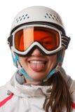 En ung snowboardflicka som bär en hjälm, och exponeringsglas satte ut hennes tunga Arkivbild
