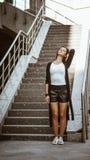 En ung spenslig flicka står nära stadstrappan och rätar ut hennes röda hår Ögon stängde sig dreamily Bär svart läder royaltyfria bilder