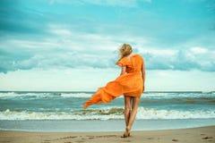En ung spenslig kvinna i orange klänning går barfota in mot det fantastiska havet Arkivfoto