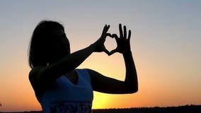 En ung Sportive kvinna gör en förälskelse att göra en gest på en storartad solnedgång arkivfilmer