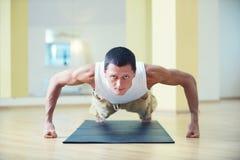 En ung stark man som gör yoga, övar - Chaturanga Dandasana fyra poserar den -lemmad personalen i yogastudion Arkivfoto
