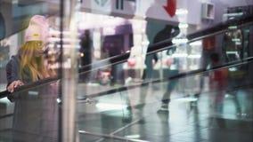 En ung stilfull hipsterkvinna klättrar en trevalator i ett lager shopping arkivfoton