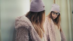 En ung stilfull hipsterkvinnlig försöker på det nya omslaget i lagret, dans och har gyckel royaltyfri fotografi
