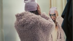 En ung stilfull hipsterkvinnlig försöker på det nya omslaget i lagret, dans och har gyckel royaltyfri foto