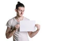 En ung stilig grabb med ett tomt ark av papper som ser ett ark Ställe för häftet, text Horisontal inrama Arkivbild