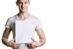 En ung stilig grabb med ett tomt ark av papper som ser ett ark Ställe för häftet, text Horisontal inrama Arkivfoton