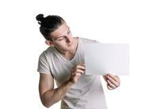 En ung stilig grabb med ett tomt ark av papper som ser ett ark Ställe för häftet, text Horisontal inrama Arkivbilder