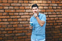En ung stilig grabb rymmer kaffe och står mot en tegelstenvägg Han är iklädda vita flåsanden, och en blå skjorta, grabben är royaltyfria bilder