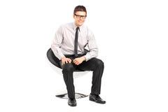 En ung stilig manlig som sitter på en stol royaltyfria foton