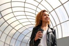 En ung svart kvinna på en gå i en stads- miljö En modern härlig afrikansk amerikanstudentflicka i ett läder arkivbilder