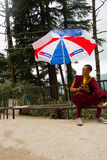 En ung tibetan buddistisk munk sitter under ett paraply i Mcleod Ganj, Indien Royaltyfria Foton
