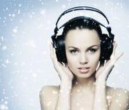 En ung tonårs- flicka som lyssnar till musik i hörlurar på snön Royaltyfri Fotografi