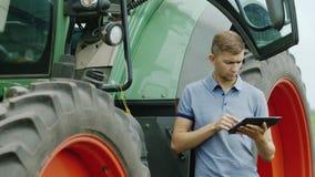 En ung traktorchaufför använder en minnestavla En bonde står nära en jordbruks- maskin lager videofilmer