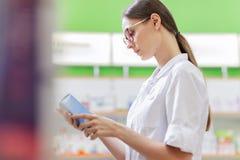 En ung tunn brunhårig flicka med exponeringsglas som är iklädda en medicinsk overall, läser något på pillrens packe bredvid arkivbilder