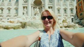 En ung turist- kvinna tar en video med henne på bakgrunden av den berömda Trevi-springbrunnen i Rome, Italien arkivfilmer