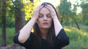 En ung uppriven kvinna rymmer hennes huvud i hennes hand och skakar det arkivfilmer