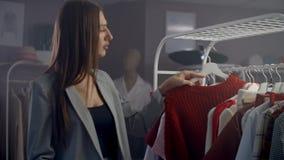 En ung vacker flicka i en klädaffär som ser klänningar och svettas på räknaren Ta från en hängare och placera lager videofilmer
