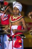 En unga cymbalspelare eller Thalampotakaruwo utför längs gatorna av Kandy i Sri Lanka under Esalaen Perahera Arkivfoto