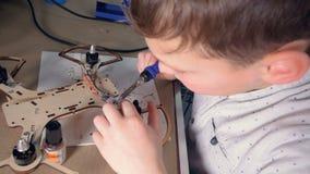 En unge arbetar på hans moderna flyggrejmodell arkivfilmer