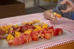 En unge tycker om att smaka de fria prövkopiorna av cutup bifftomater på de lokala bönderna marknadsför royaltyfri bild