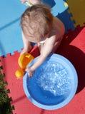 En ungt barn som leker med, bevattnar Arkivbild