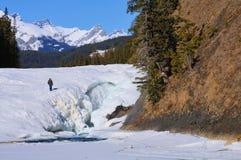 En unidentifiable man som går på en djupfryst pilbågenedgång i den Banff nationalparken i kanadensaren Rocky Mountain, arkivfoton