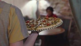 En uppassare bär en stor smaklig aptitretande pizza för rund ost till en kund lager videofilmer
