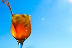 En uppfriskande drink med is och sugrör i exponeringsglas på en bakgrundshimmel och sol Arkivfoto