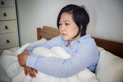 En uppriven kvinna som grubblar i säng Arkivfoto