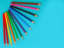 En uppsättning av barn, kulöra blyertspennor på en turkosbakgrund arkivbild