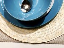 En uppsättning av bestick: en sked och blåttplattor på en trätabell Workpiece på en träbakgrund Arkivfoto