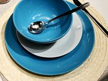En uppsättning av bestick: en sked och blåttplattor på en trätabell Workpiece på en träbakgrund Arkivbilder