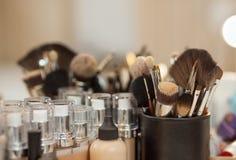 En uppsättning av borstar för smink och tonar fundamentet för personanseendet på tabellen framme av en spegel i en skönhetsalong Arkivbilder