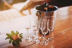 En uppsättning av champagneexponeringsglas med ishinken av champagneflaskan på trätabellen med varm belysning från vänster sida arkivfoto
