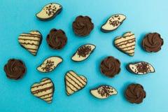 En uppsättning av chokladgodisar i olika former som isoleras på en blå bakgrund arkivbild