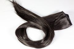 En uppsättning av förlängningar för svart hår av lockigt hår för den rödaktiga brunetten på en skönhet shoppar tabellen arkivfoton