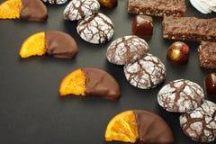 En uppsättning av hemlagade sötsaker: nissen, marshmallower, kakor, marmelad, läckra skivor av apelsinen i choklad och godisar arkivbilder