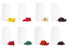 En uppsättning av kapslar bredvid en vit plast- medicinflaska Arkivbild