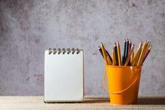 En uppsättning av kulöra blyertspennor på en leksakhink och en tom liten anteckningsbok Arkivbilder