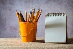 En uppsättning av kulöra blyertspennor på en leksakhink och en tom liten anteckningsbok Royaltyfria Bilder