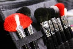 En uppsättning av makeupborstar i ett fall Borstar svart, rött och vitt arkivbilder