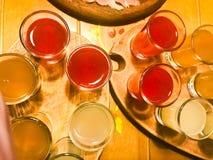 En uppsättning av massor av läckra gula orange röda exponeringsglas, skott med stark alkohol, vodka, fyllning, konjak på träställ arkivbilder