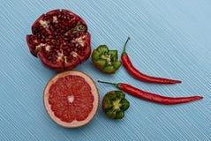 En uppsättning av nya mogna frukter och röda peppar på en blå tabell Royaltyfria Bilder