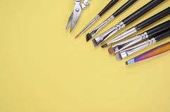 En uppsättning av olika borstar för makeupkonstnär och saxen ligger i ett hörn med copyspace för text på gul färg arkivbilder