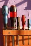 En uppsättning av olika skruvmejslar i en träsjälv-gjord hållare på väggen Fotografering för Bildbyråer