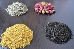 En uppsättning av olika teer - rosa färg, svart som är växt-, guling royaltyfria bilder