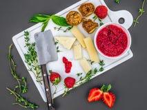 En uppsättning av ost, nya jordgubbar, örter, torkade fikonträd och raspb Arkivbild